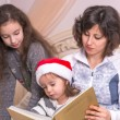 Mom reading a Christmas story with children. — Stock Photo #59014267