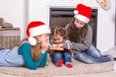 Elder sisters reading a Christmas story his little sister. — Stock Photo