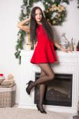 Girl in a short red dress on background Christmas decorations — Stock Photo