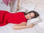Ung kvinna i en röd klänning på sängen — Stockfoto