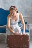 Girl in retro style wedding dress collects a vintage suitcase in — Stock Photo