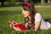年轻的女孩,一个记事本和笔中夏公园 — 图库照片