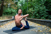 Happy Athletic man doing yoga asanas in the park at sunny day — Stock Photo