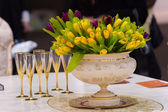 Vintage vase with tulips and champagne glasses — Stock Photo
