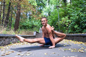 Handsome smiling flexible Athletic man doing yoga asanas in the park — Stock Photo