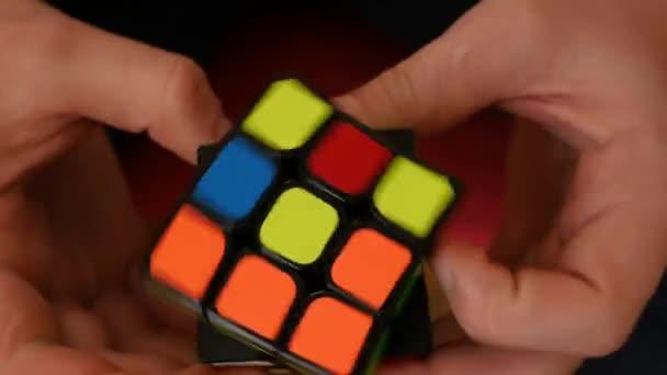 Muchacho joven rápidamente y correctamente soluciona cubo de Rubik — Vídeo de stock