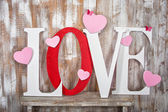 Love word with hearts on wooden planks background — Stock Photo