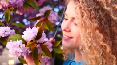 Young woman smelling cherry blossom — Stock Video