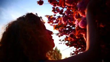 Young woman and cherry blooming at sunset — Stock Video