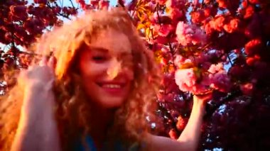Young woman and cherry blossom at sunset — Stock Video