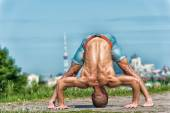 Athletic man doing yoga asanas in the park at sunny day — Stock Photo