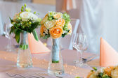 Flower bouquets on wedding dining table — Stock Photo
