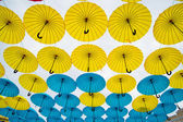 Bright colorful yellow and blue umbrellas background — Stock Photo