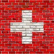 Grunge flag of Switzerland on a brick wall — Stock Vector #78264472