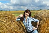 Woman near haystacks — Stock Photo