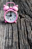 Small pink watch on wood background. — Stock Photo
