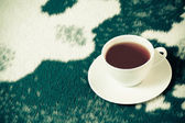 Vintage cup of tea on the blanket — Stock fotografie