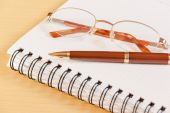 Pen, notebook and glasses. Selective focus on pen — Stockfoto