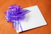 Close up of a note card with violet bow on wooden background — 图库照片