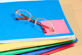 Group of multicolored office folders and glasses — Stock Photo