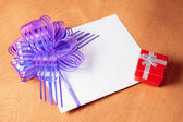 Close up of a note card with violet bow and red gift box on wood — Stock Photo
