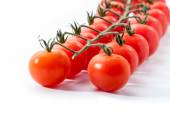 Red tomatoes with branch on white — Stockfoto