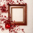 Classic wooden frame decorated with Christmas foil stars and red ball — Stock Photo #60498817