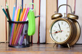 Pencils and clock on shelf — Stock Photo