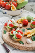 Toasted bread topped (Bruschetta) with grilled zucchini, mozzarella, cherry tomatoes. Italian cuisine. — Stock Photo