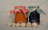 Jars of jam and nuts on old canvas — Stock Photo