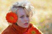 Mooie vrouw buiten portret op een zonnige dag en rode bloemen — Stockfoto