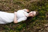 Beautiful innocent woman in white dress lying on the grass — Stockfoto