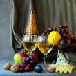 Two glasses of wine, cheese and ripe fruit — Stock Photo #52991055