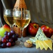 Two glasses of wine, cheese and ripe fruit — Stock Photo #52991057