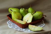 Green pears in a basket and one of them cut into the share — Foto de Stock