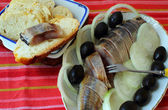 Plate of herring, decorated with olives and onion rings and bread — Stock Photo