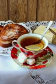 Taza de té, pan y mantequilla sobre un mantel blanco — Foto de Stock