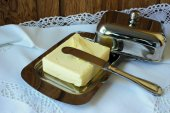 Butter in the butter-dishand and knife on a white tablecloth — Foto de Stock