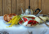 Cup of tea, teapot and  buns  on a white tablecloth — Foto de Stock