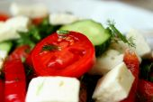 Tomatoes, cucumbers and feta cheese in a salad closeup — Stock Photo