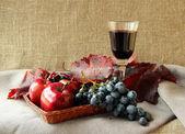 Glas rött vin och massa druvor — Stockfoto