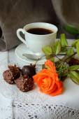 Rosebud, a cup of coffee and sweets — Stock Photo