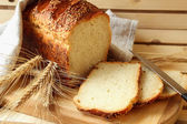 Homemade bread and stalks of wheat — Stock Photo
