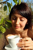 Beautiful girl holding a cup of tea on a background of nature — Stock Photo
