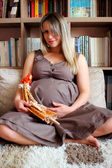 A young pregnant woman sitting in a room with soft doll — Stock fotografie