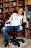 Young pregnant woman sitting on a chair — Stock fotografie