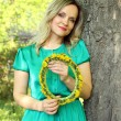 Beautiful girl with a wreath of dandelions in the hands of — Stock Photo #72557747
