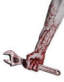 Halloween theme: bloody hand holding a big wrench on a white background — Stockfoto