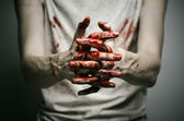 Bloody theme lone murderer: the murderer shows bloody hands and experiencing depression and pain — Stock Photo