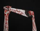 Halloween theme: bloody hand holding a bloody saw on a black background — Stock Photo